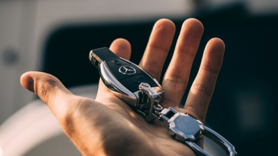A hand holding a Mercedes-Benz key fob.