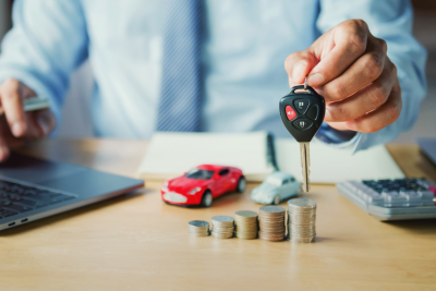 A hand holding a key fob, with blurred toy cars and coins in the background.