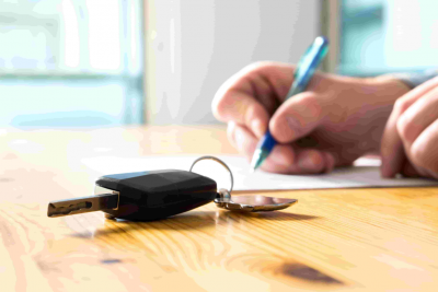 Man signing a purchase contract with car keys on the table.