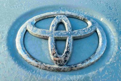 A silver Toyota emblem on the hood of a sky-blue car.