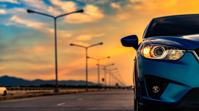 A blue hybrid vehicle from a used car dealer in Auckland, set against the backdrop of a sunset.