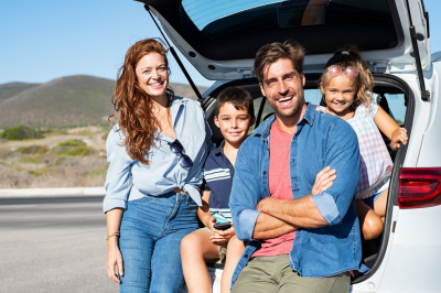 Smiling New Zealand family with two kids sitting in Japanese used car trunk and looking at camera