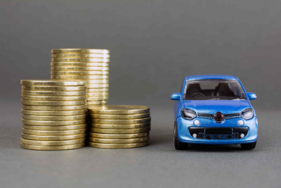 A toy car sitting next to a stack of gold coins.