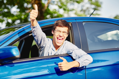 Close up of a teenager wearing glasses showing the thumb up hand gesture and happy through car window, after buying used car