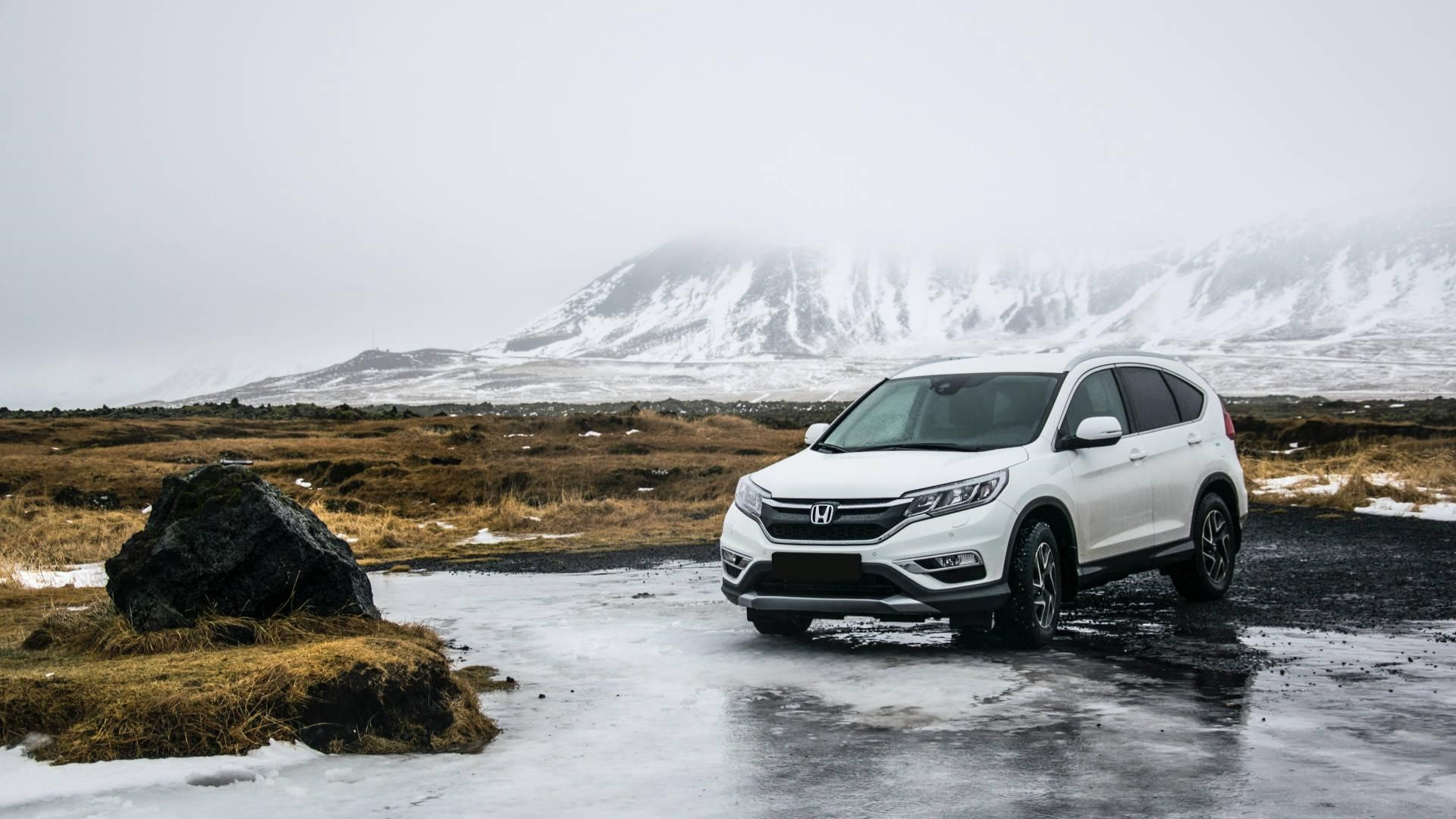 A Honda used car, parked in front of snow-capped mountain backdrop
