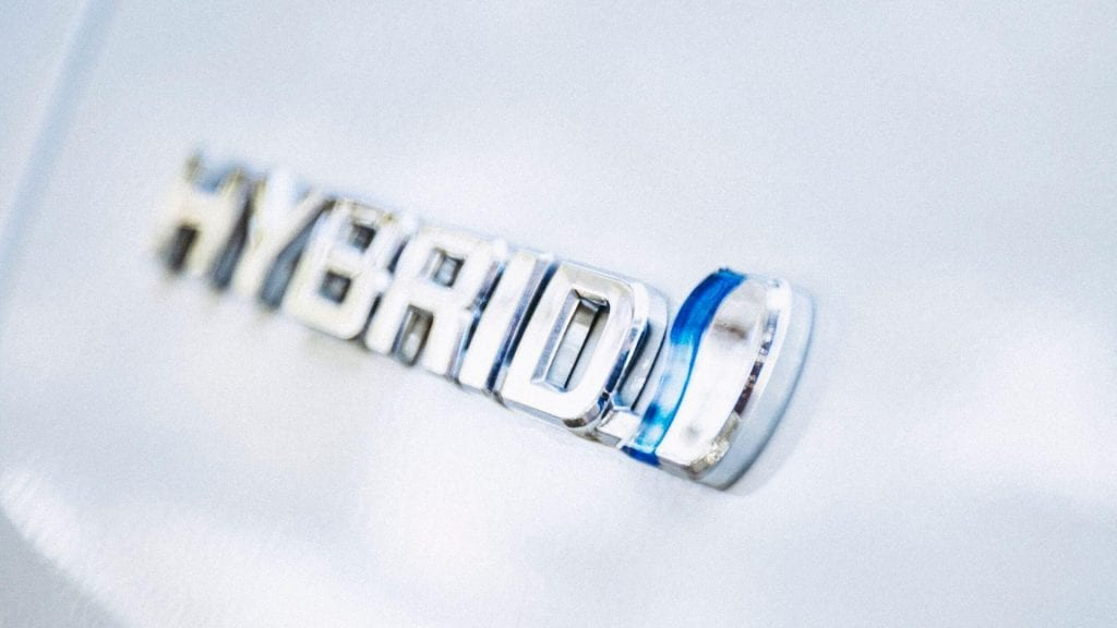 "A close-up of a hybrid used car's ""hybrid"" logo"