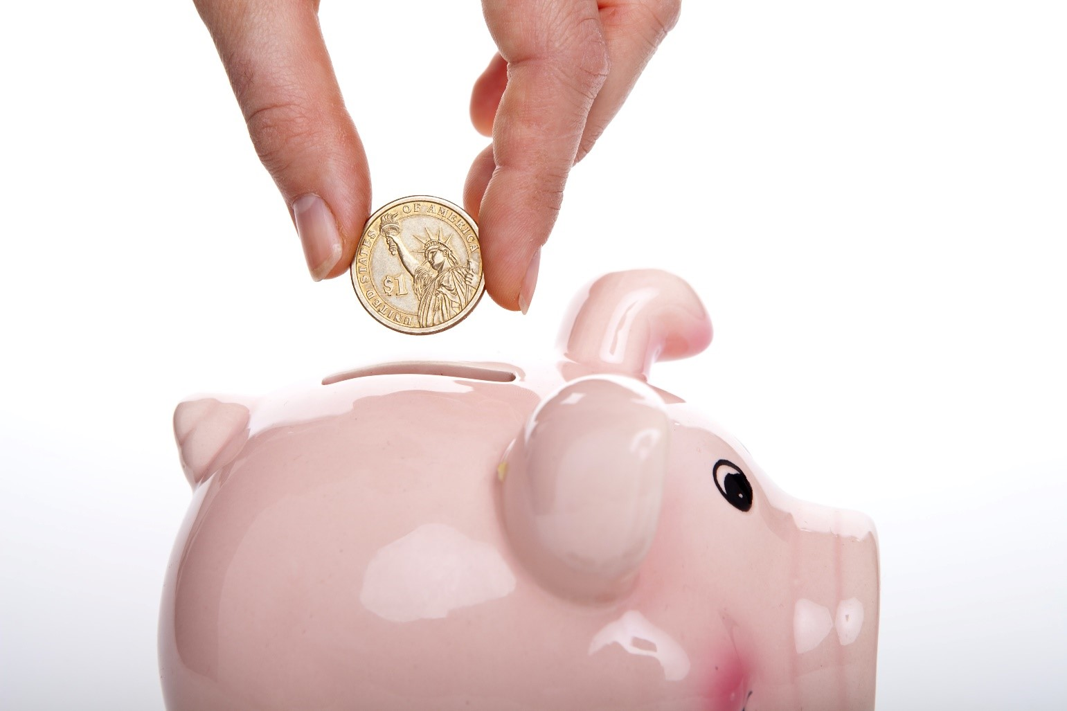 A hand placing a coin into a pink piggy bank.