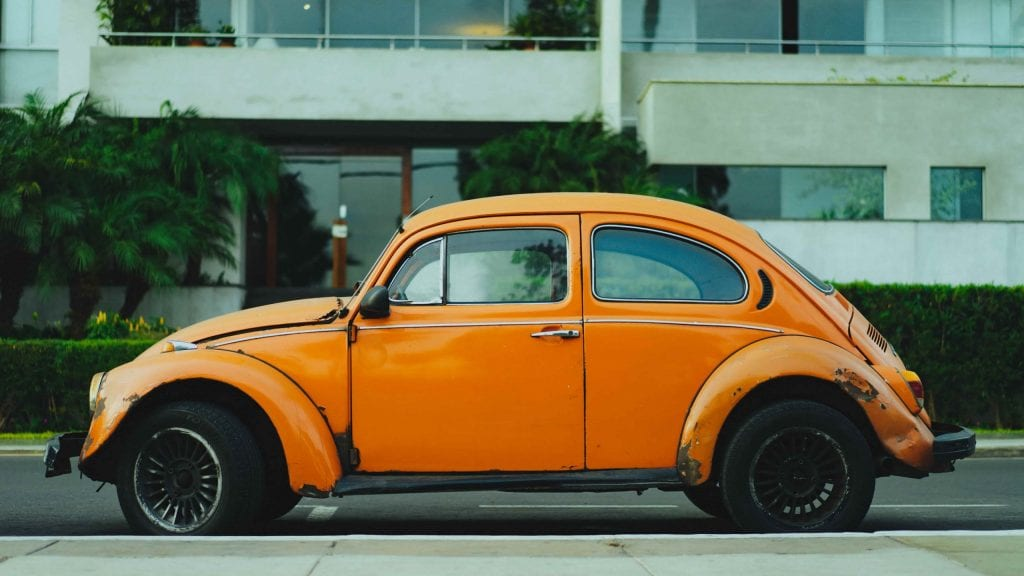 An old, orange Volkswagen Beetle; the type of second-hand vehicle most people don't want.