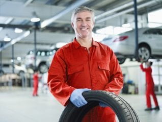 Portrait of smiling mechanic holding tire in auto repair shop