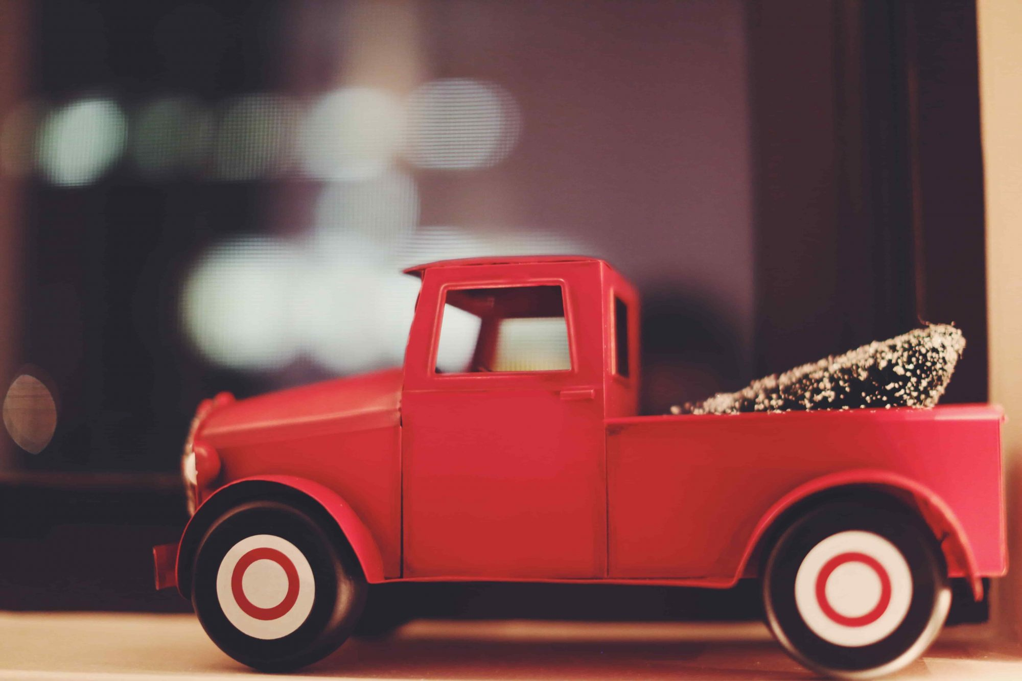 A red plastic pickup truck with a fake Christmas tree in the back.