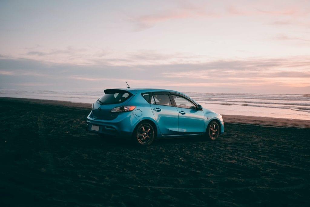 Blue mazda axela on beach facing the ocean sunset
