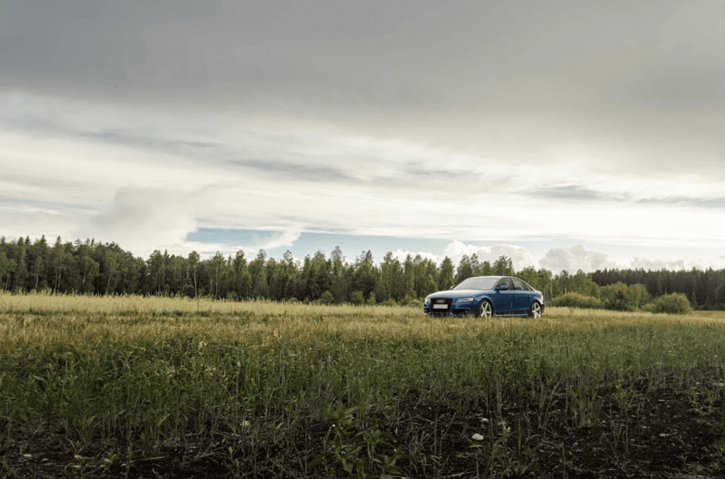 Blue car driving along grassy countryside road