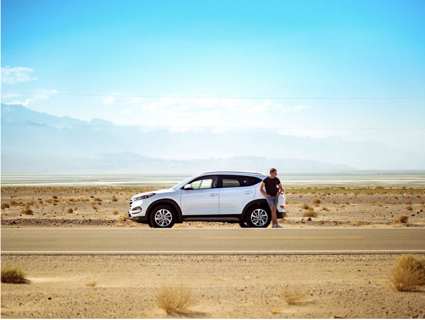 Man with broken down car on side of road with blue sky in background