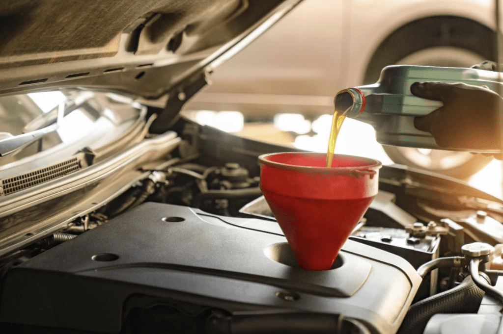 Engine Oil being poured into engine of car by mechanic