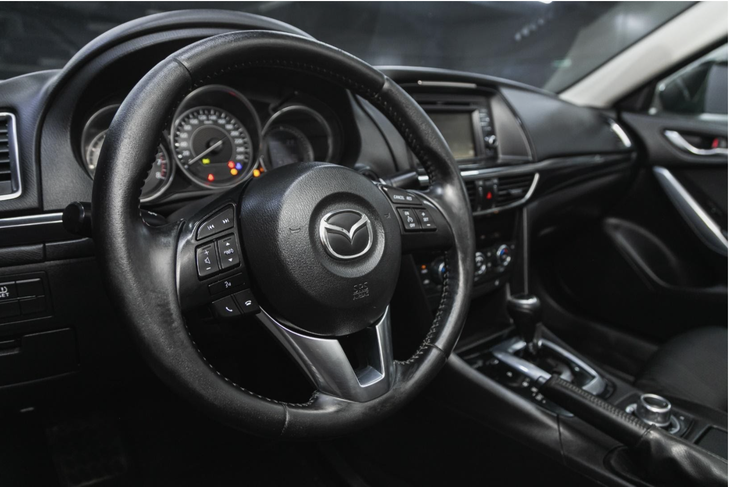 Mazda Car badge on steering wheel with dashboard in background